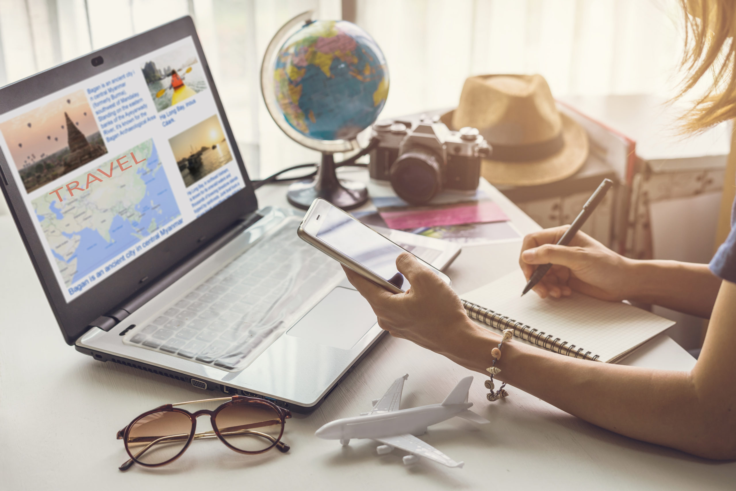 Young woman planning vacation trip and searching information or booking an hotel on a smart phone and laptop