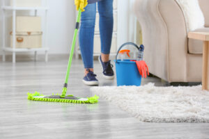 Female janitor mopping floor in room
