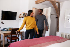 Couple Spending Romantic Weekend Away Opening Door Of Hotel Room - The Magic Helpers Airbnb Cleaning Services